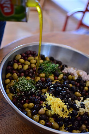 Finishing touches on spiced olives